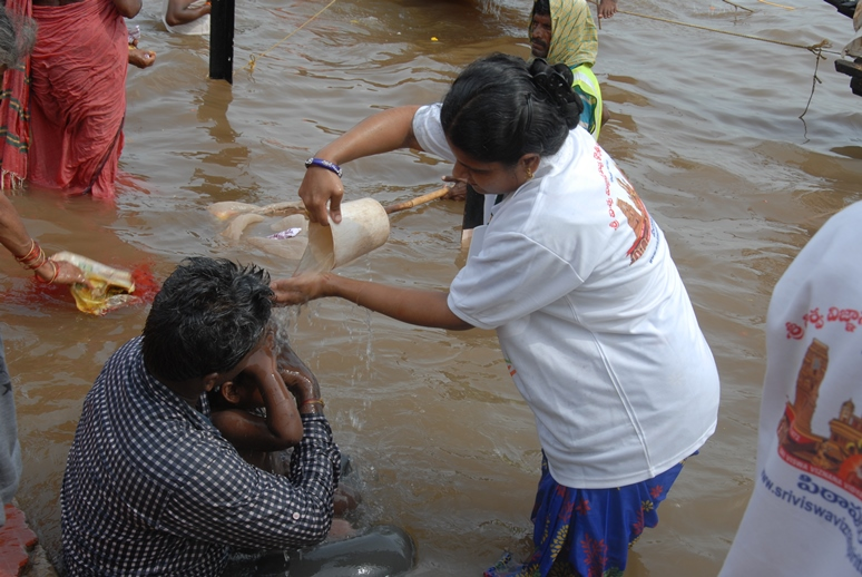 3rd shift volunteer providing helping child at Gowthami ghat