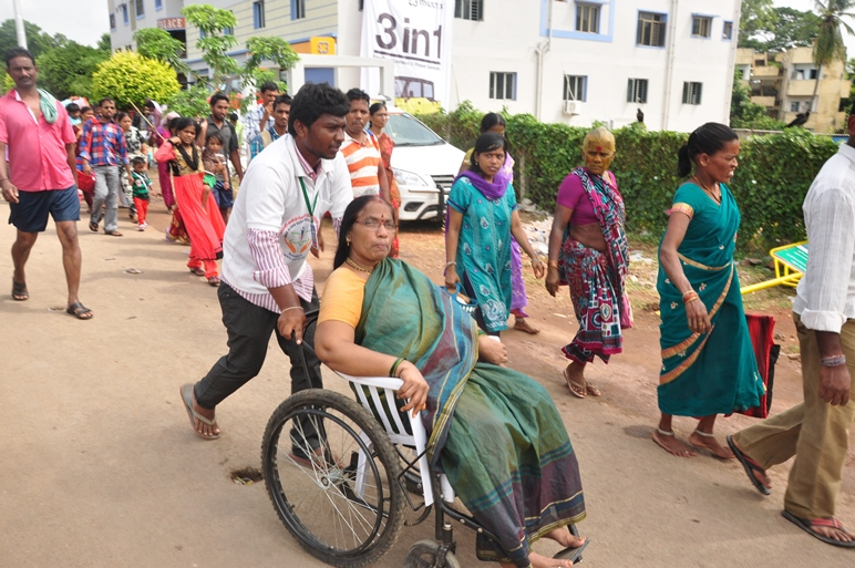 Volunteers taking elderly on wheel chair from Kailasa bhoomi to Gowthami ghat, Rajahmundry on 20th Jul 2015, 7th day of Godavari Pushkaralu