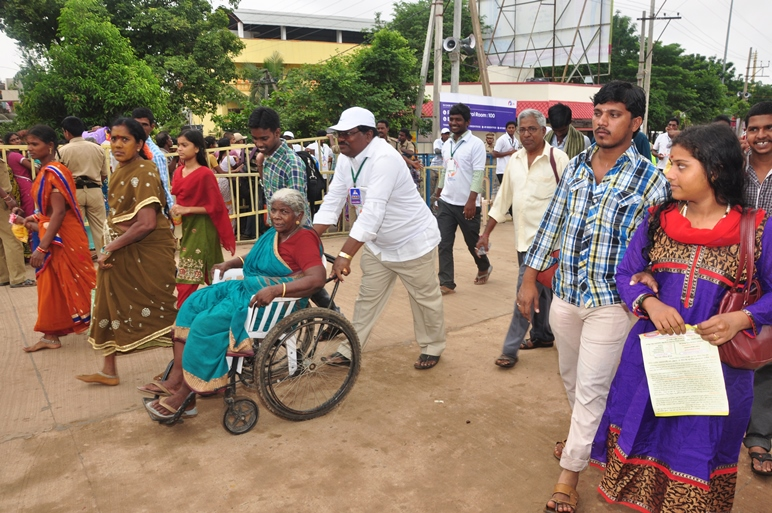 Volunteer assisting elderly with wheel chair  at Gowthami ghat, Rajahmundry on  23 Jul 2015, 10th day of Godavari Pushkaralu