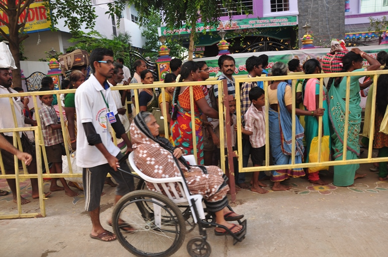 Volunteer assisting elderly with wheel chair on 24 Jul 2015, 11th day of Godavari Pushkaralu at Gowthami ghat